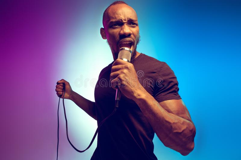 Young african-american jazz musician singing a song. On gradient purple-blue background. Concept of music, hobby. Joyful attractive guy improvising, having a stock image