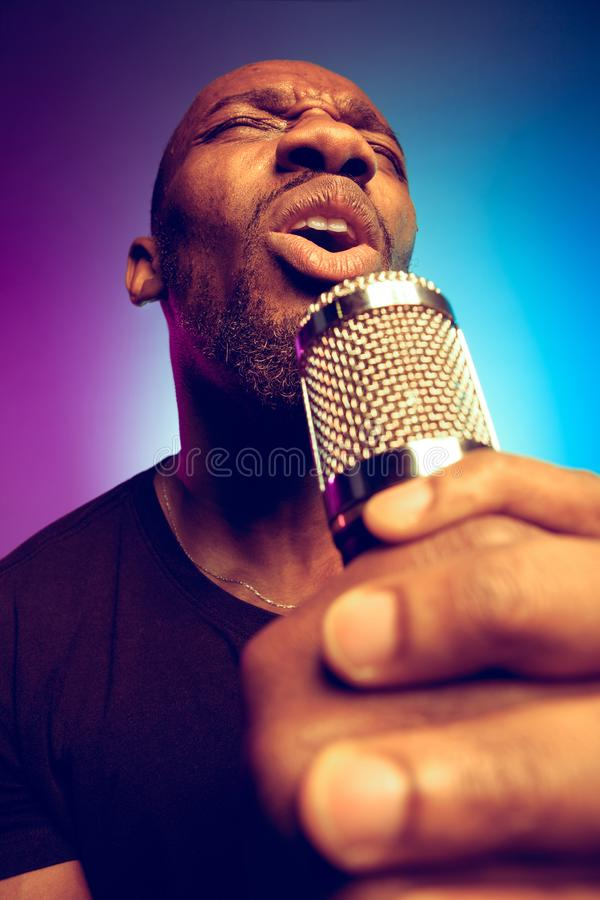 Young african-american jazz musician singing a song. On gradient purple-blue background. Concept of music, hobby. Joyful attractive guy improvising, having a stock images