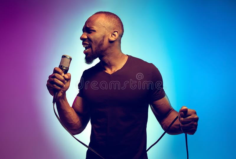 Young african-american jazz musician singing a song. On gradient purple-blue background. Concept of music, hobby. Joyful attractive guy improvising, having a royalty free stock images