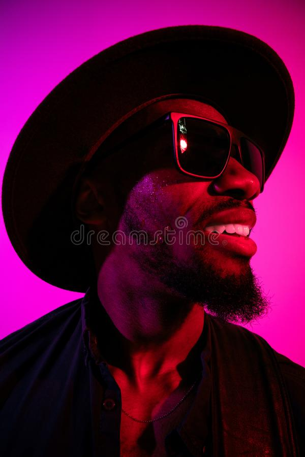 Young african-american jazz musician singing a song. On gradient purple-pink background. Concept of music, hobby. Joyful attractive guy improvising, having a royalty free stock images