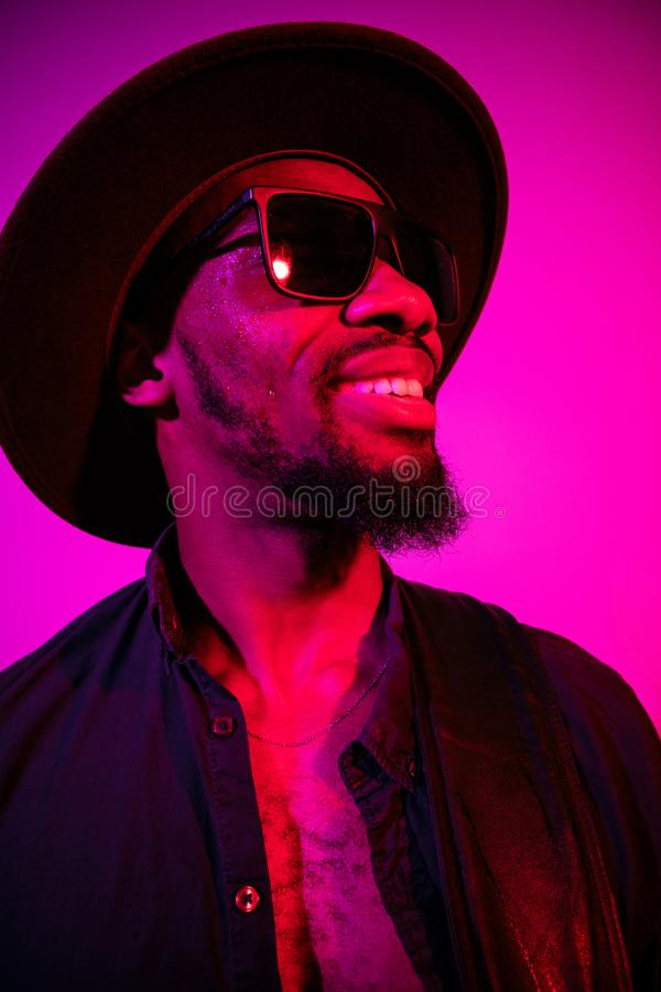 Young african-american jazz musician singing a song. On gradient purple-pink background. Concept of music, hobby. Joyful attractive guy improvising, having a royalty free stock photo