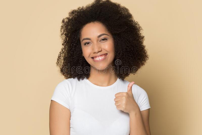 Young african american lady showing like, thumbs up gesture. Head shot close up studio portrait young african american lady showing like, thumbs up gesture royalty free stock photo