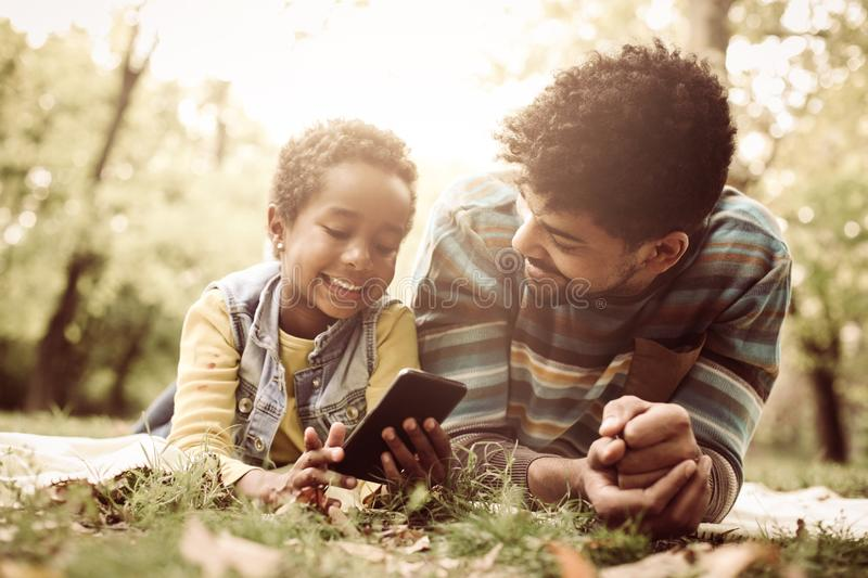 Young African American little girl and her father lying down in royalty free stock photo