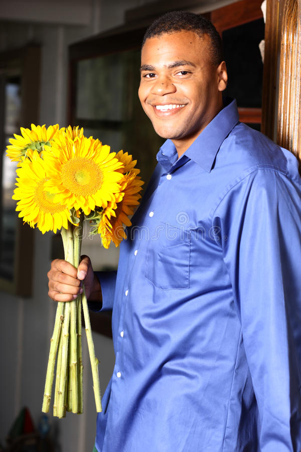Young African American Male with Sunflowers royalty free stock photo