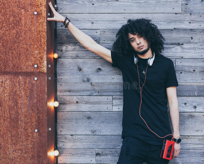 Young African American man with an afro hairstyle as DJ posing on wooden background. Headphones and red vintage cassette. Player. Wearing a black outfit royalty free stock photography