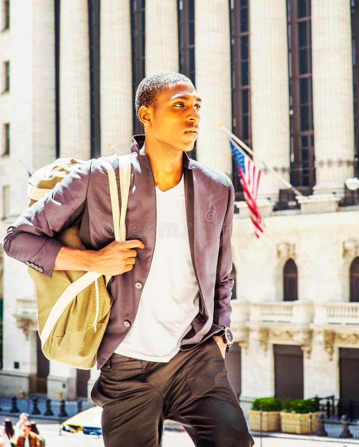 Young African American Man carrying shoulder bag, traveling in N royalty free stock photography