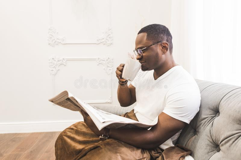 Young African American man, covered with a blanket reading a newspaper at home. stock photos