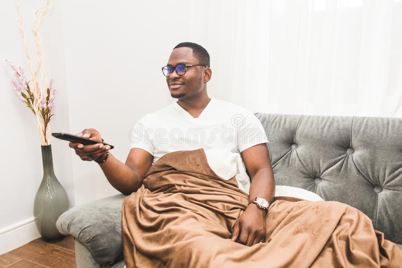 Young African American man, covered with a blanket, watching TV at home. stock photo