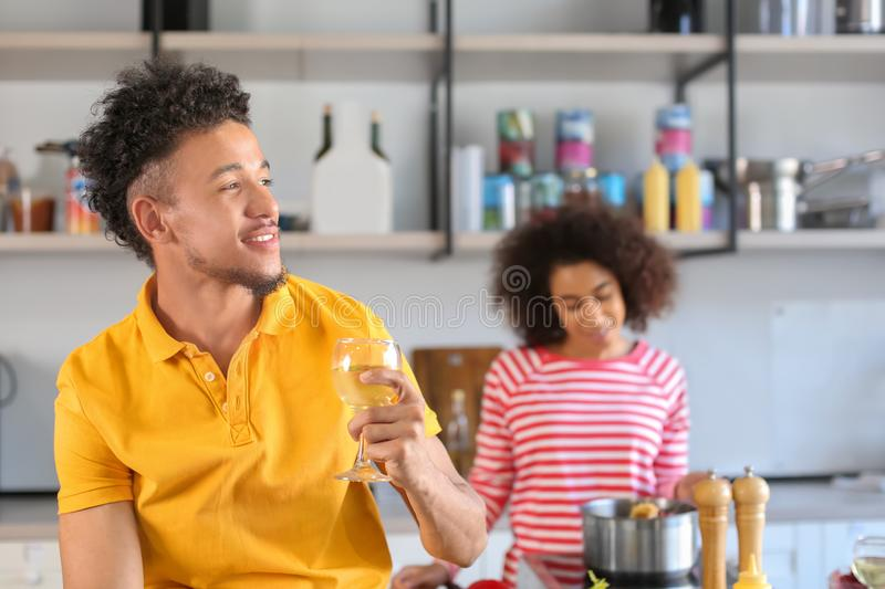 Young African-American man drinking wine and his girlfriend cooking in kitchen. Young African-American men drinking wine and his girlfriend cooking in kitchen stock photo