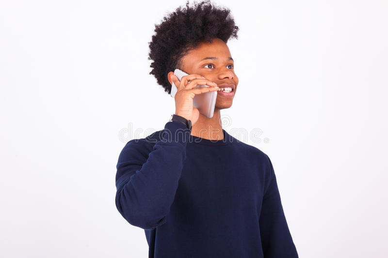 Young African American man making a phone call on her smartphone. Black teenager people stock photo
