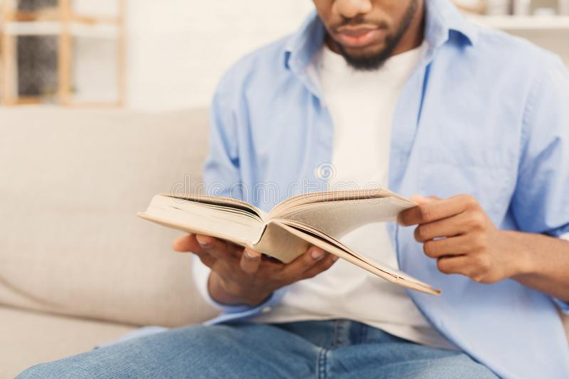 Young african-american man reading book at home royalty free stock image