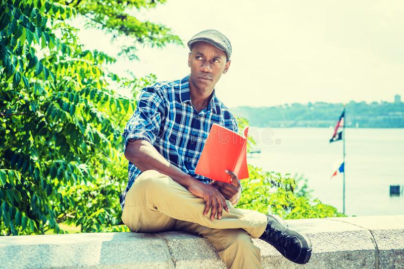 Young African American Man reading red book, relaxing outdoor in. New York, wearing blue, white patterned shirt, flat cap, sitting on stone fence by Hudson royalty free stock image