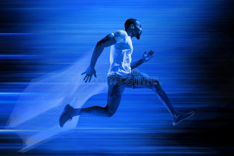 Young african-american man running isolated on blue studio background stock photography