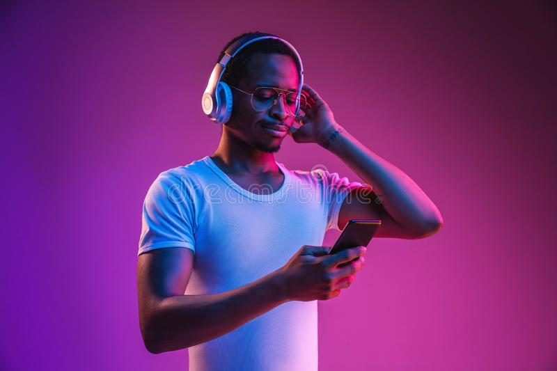 Young african-american man`s listening to music in neon light stock photography