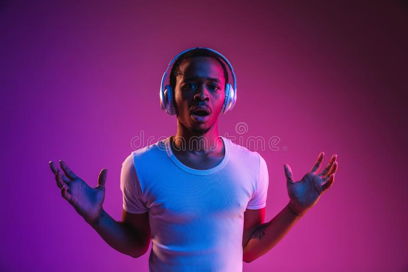 Young african-american man`s listening to music in neon light royalty free stock photography
