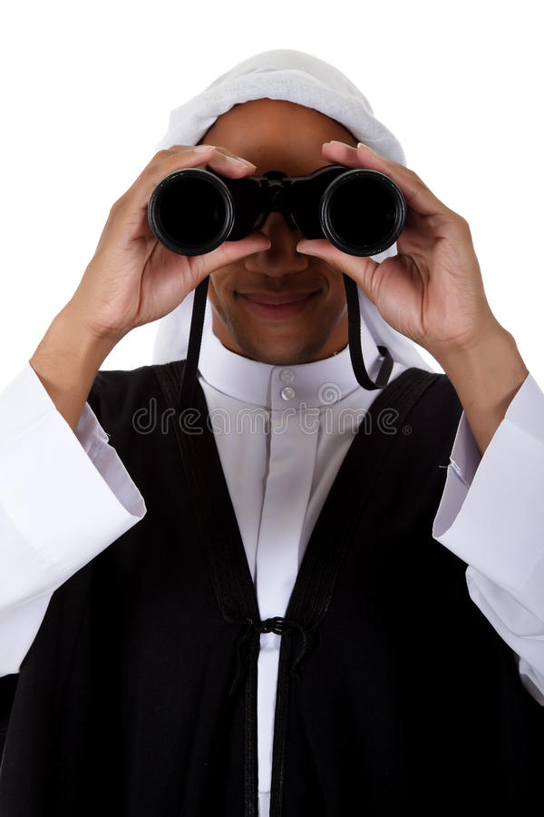 Young African American man, sheikh, binoculars. Young attractive African American man in sheikh posture dressed in arab garb, looking through binoculars. Studio royalty free stock photography