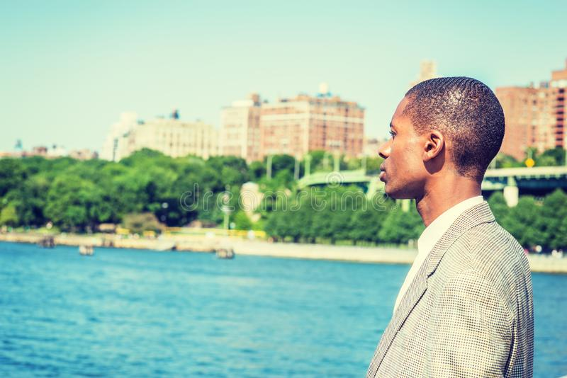 Young African American Man with short hair, traveling in New York City. Standing by Hudson River in Manhattan under sun, looking, waiting, thinking. Green royalty free stock images