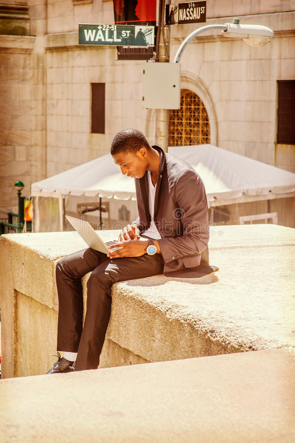 Young African American Man traveling, working on Wall Street in. Young African American man traveling, working in New York. Young black college student sitting royalty free stock photo