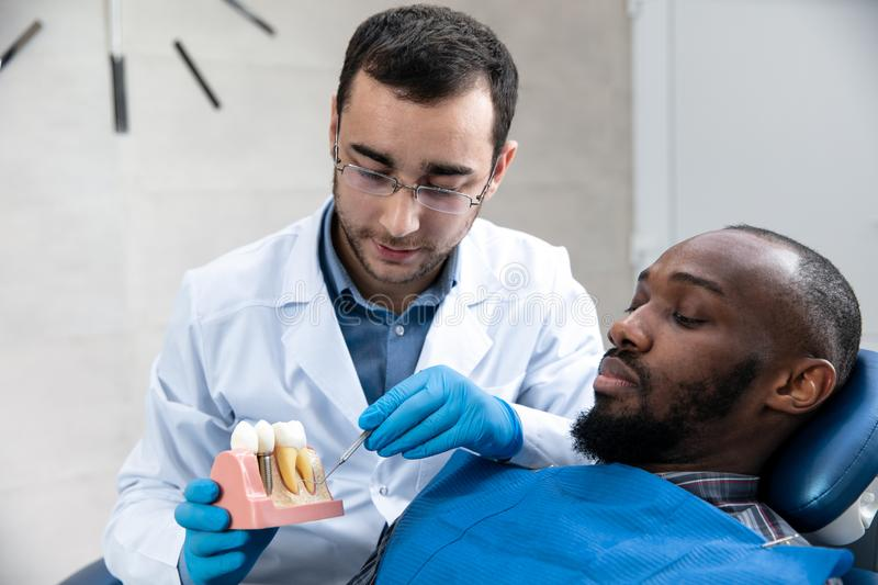 Young african-american man visiting dentist`s office royalty free stock photography
