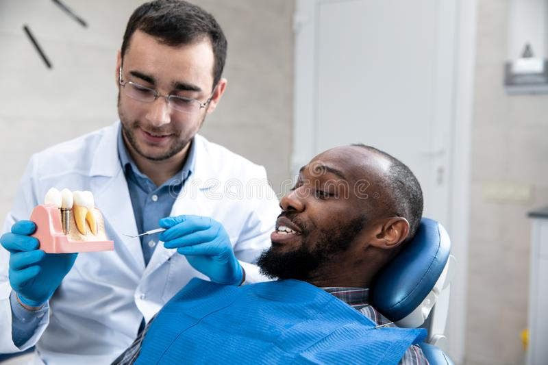 Young african-american man visiting dentist`s office stock photo