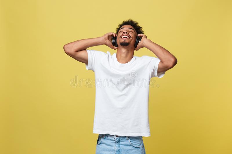 Young African American man wearing headphone and enjoy music over yellow gold Background.  royalty free stock image