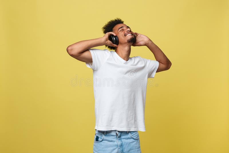 Young African American man wearing headphone and enjoy music over yellow gold Background.  stock images