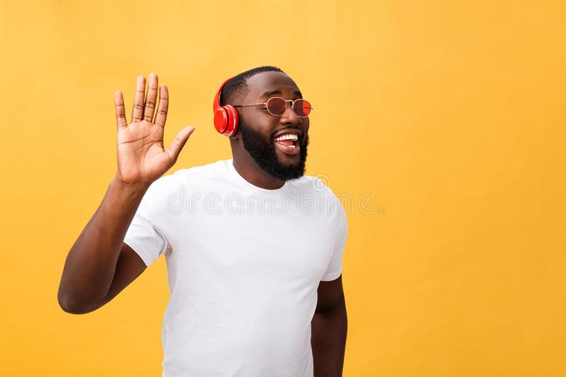Young African American man wearing headphone and enjoy music over yellow gold Background.  stock photo