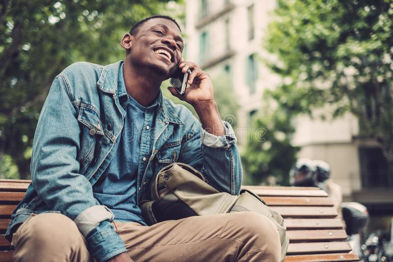 Young african-american with mobile phone outdoors royalty free stock photography