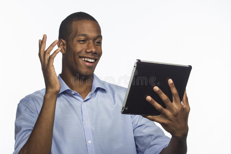 Young African American using an electronic tablet, horizontal. Young black man using an electronic tablet and posed against white background stock photos