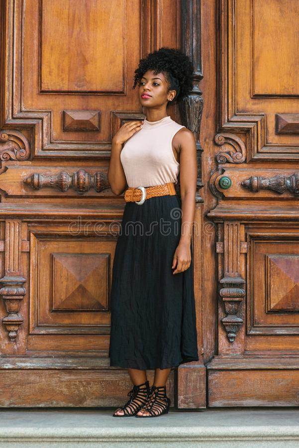 Young African American Woman Casual Fashion in New York, with afro hairstyle, wearing sleeveless light color top, black skirt, stock image