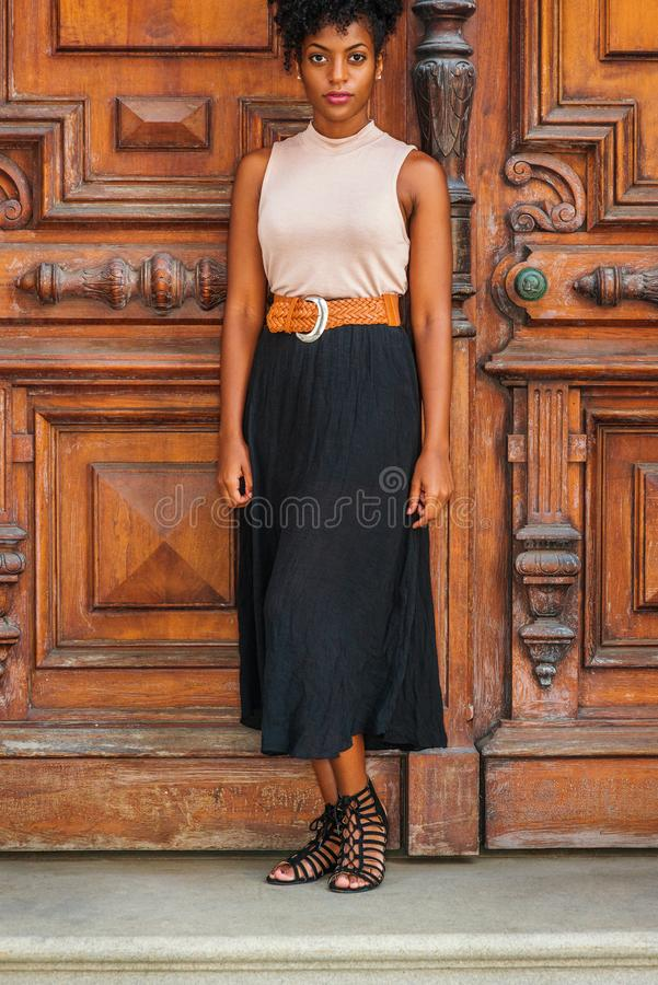 Young African American Woman Casual Fashion in New York, with afro hairstyle, wearing sleeveless light color top, black skirt,. Dark orange belt, strappy stock image