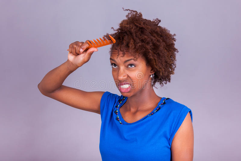 Young African American woman combing her frizzy afro hair - Blac royalty free stock photos