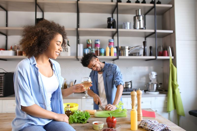Young African-American woman drinking wine and her boyfriend cooking in kitchen. Young African-American women drinking wine and her boyfriend cooking in kitchen stock image