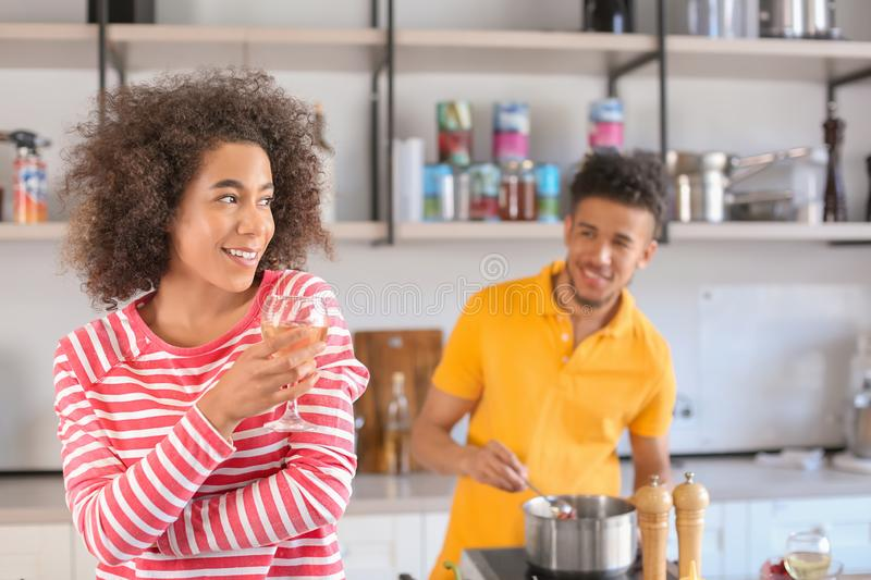 Young African-American woman drinking wine and her boyfriend cooking in kitchen royalty free stock photos