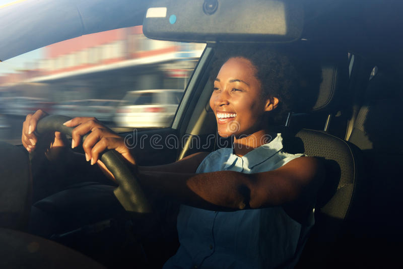 Young african american woman driving a car. Portrait of smiling young african american woman driving a car stock photos