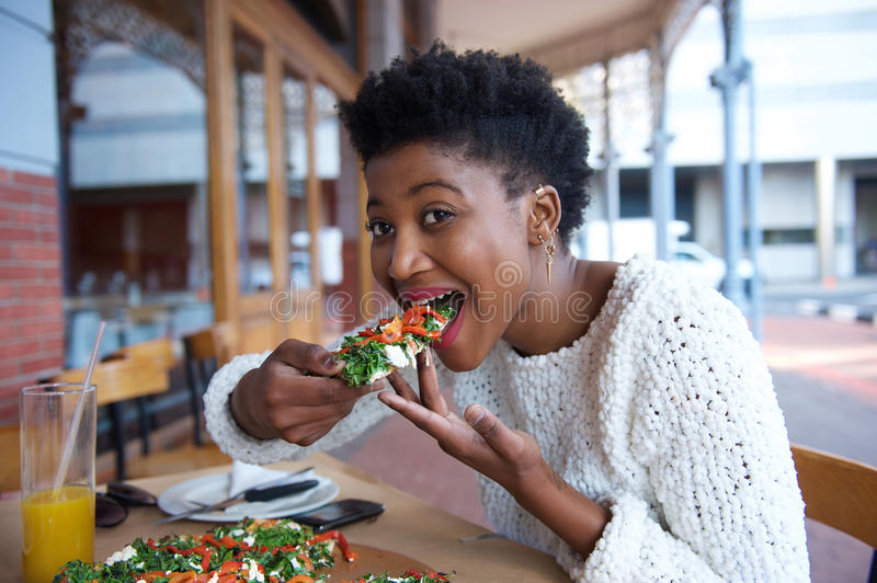 Young african american woman eating pizza royalty free stock image
