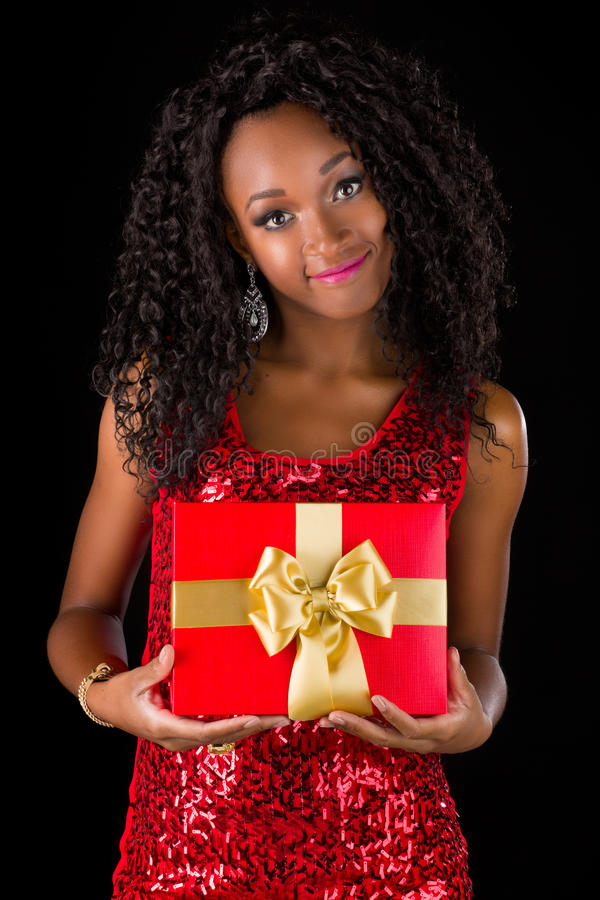 Young african-american. Woman with gift isolated in studio stock images