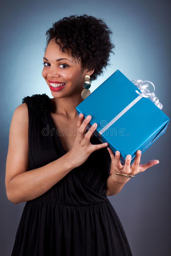 Young African American woman holding a gift royalty free stock photography