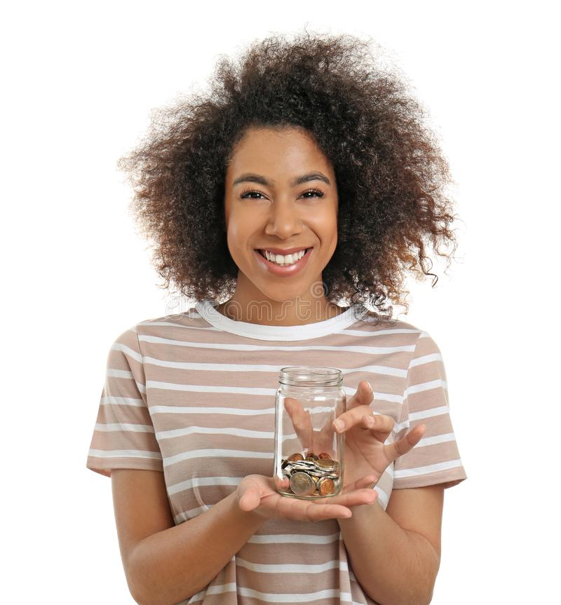 Young African-American woman holding glass jar with coins on white background. Savings concept stock photos
