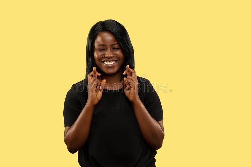 Young african woman isolated on yellow studio background, facial expression stock images