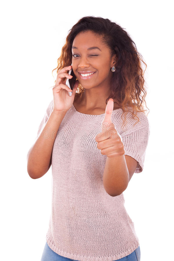 Young African American woman making a phone call on her smartphone making thumbs up gesture - Black teenager people royalty free stock image