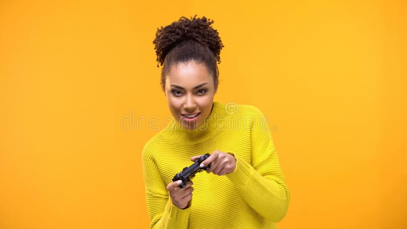 Young african-american woman playing video games with game controller, fun. Stock photo stock photography