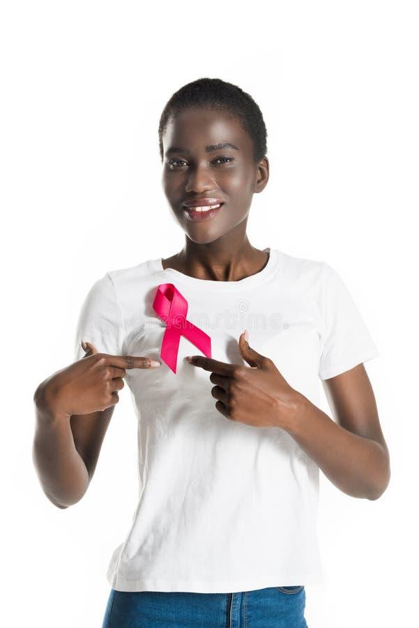 young african american woman pointing at pink ribbon and smiling at camera royalty free stock photo