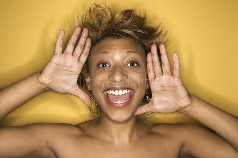 Young African-American woman portrait. Portrait of young African-American adult woman on yellow background yelling at the viewer royalty free stock photography