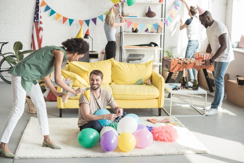 Young african american woman proposing party hat to smiling man on floor with balloons and woman. With friend royalty free stock photos