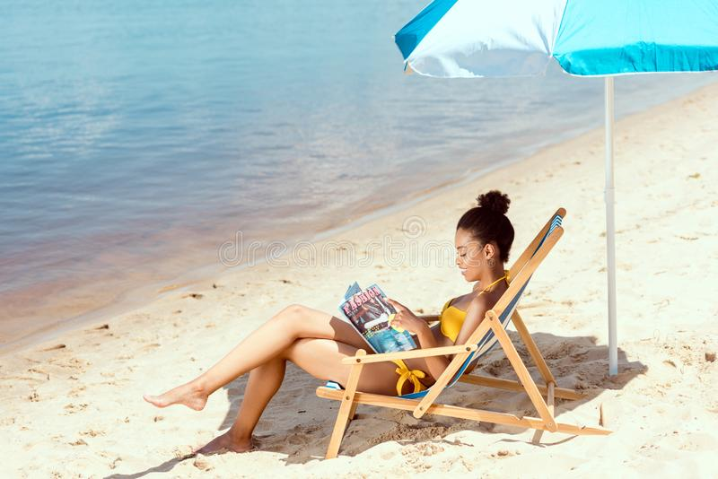 young african american woman reading magazine and relaxing on deck chair under beach umbrella in front royalty free stock photos
