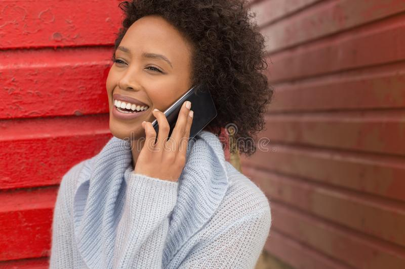 Young African American woman talking to mobile phone at beach hut royalty free stock photo