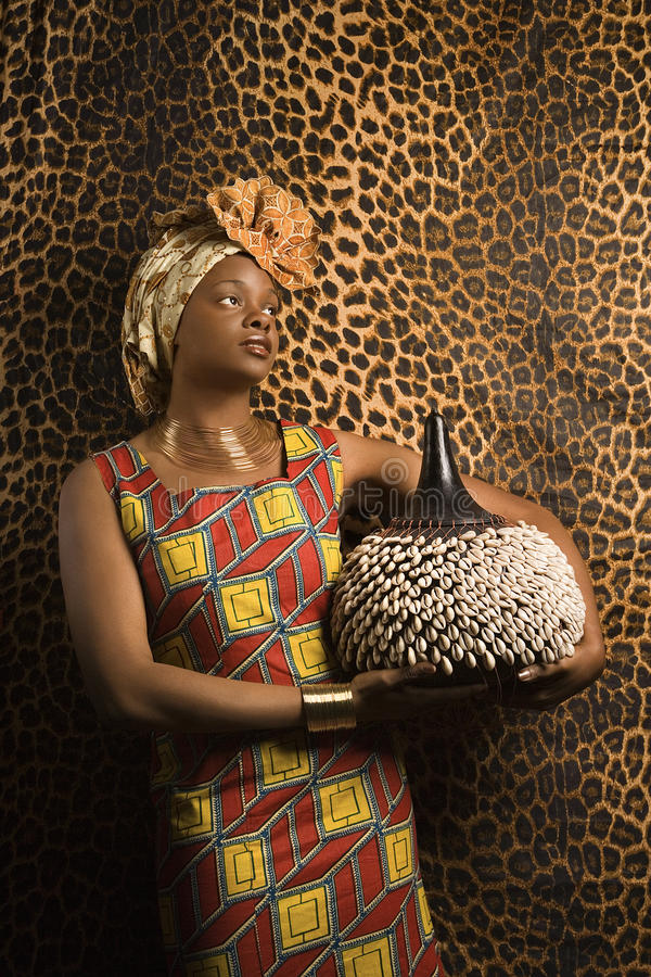 Portrait Of An African American Woman Wearing Traditional Clothing And Holding A Shekere In Front Patterned Wall Vertical Format