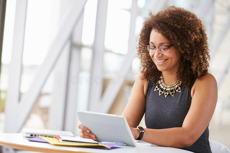 Young African American woman working with tablet in office royalty free stock photography