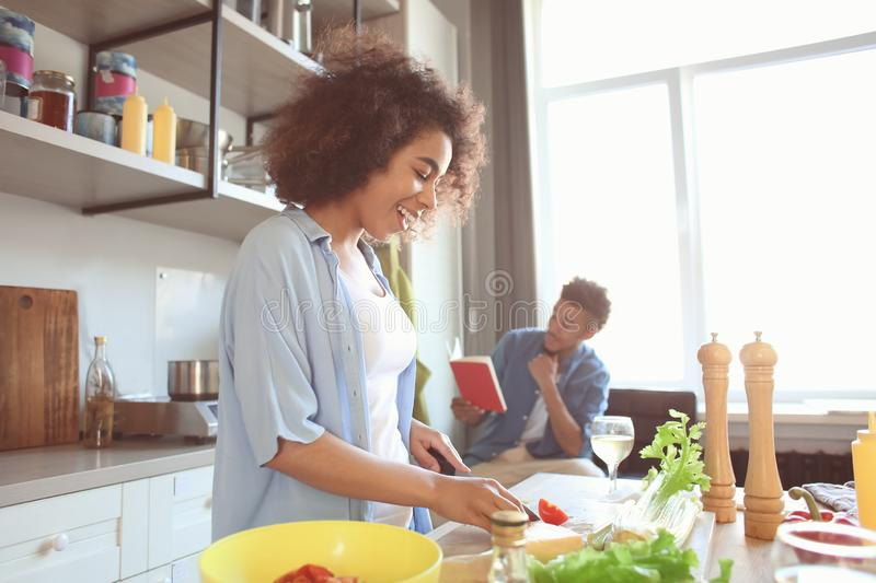 Young African-American woman cooking meal and her boyfriend reading recipe book in kitchen. Young African-American women cooking meal and her boyfriend reading stock photography